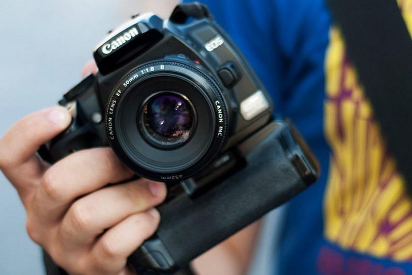 Mano de una chica con una cámara réflex digital