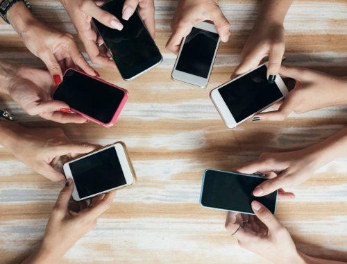 Smartphones de diferentes modelos en manos de sus dueños con la pantalla arriba