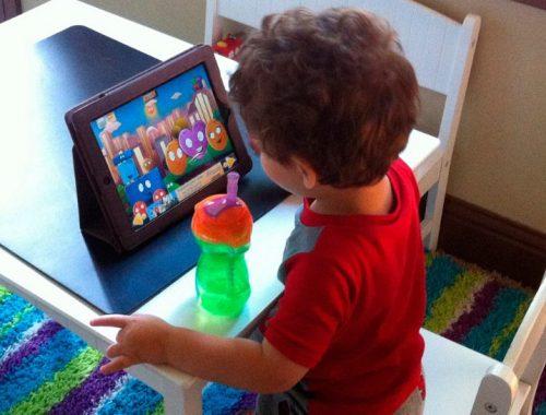 Niño pequeño viendo y escuchando música en una tablet