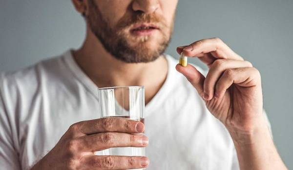 hombre tomando pastilla paracetamol