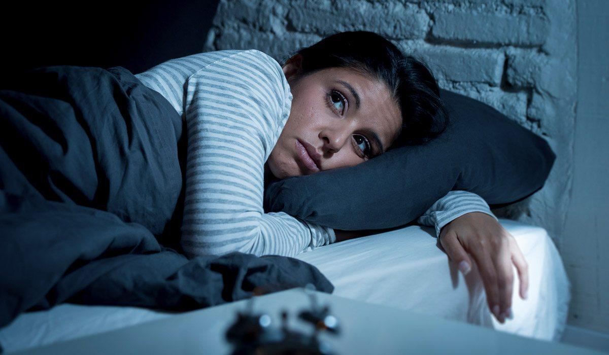mujer en su cama con insomnio