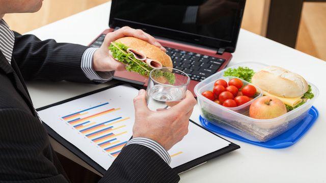 Empleado comiendo sándwich y comida para llevar al trabajo