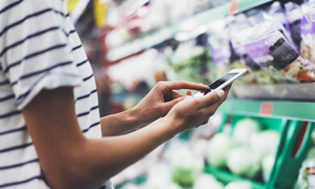 Mujer comparando precios en supermercado