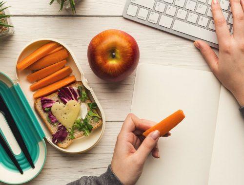 Escritorio con comida para llevar al trabajo como fruta y verduras
